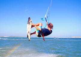 During the Private Kitesurfing Lessons in Fuseta for All Levels with Kite Culture Algarve, an advanced kitesurfer is practicing some jumps on the flat water of the Fuseta Lagoon.