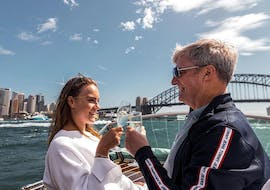 A couple is enjoying the views with a glass of champagne during the Private Luxury Boat Cruise in Sydney - Culinary Experience organised by Sydney Luxury Cruise.