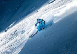 Un skieur skie au milieu de la poudreuse pendant son Cours particulier de ski freeride - Tous niveaux avec l'école de ski ESI Valfréjus.