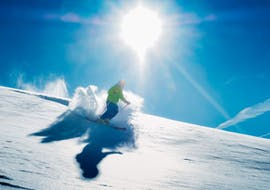 A skier is riding fresh powder during the Private Off-Piste Skiing Lessons – for Adults - Christmas under the guidance of an experienced ski instructor from the ski school Scuola di Sci B.foxes.