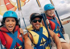 During the Private Parasailing in Paihia - For up to 12 People, 3 friends are having fun on a private boat from Bay of Islands Parasail.