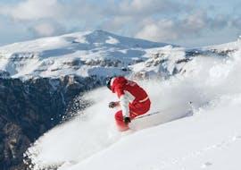 Un maestro di sci della Carezza Skischool dimostra come scendere la pista al meglio durante le Lezioni private di sci per adulti - Tutti i livelli.