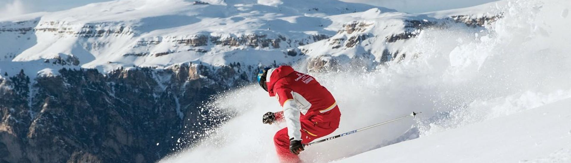 A ski instructor from Carezza Skischool is demonstrating how to ski during Private Ski Lessons for Adults - All Levels.