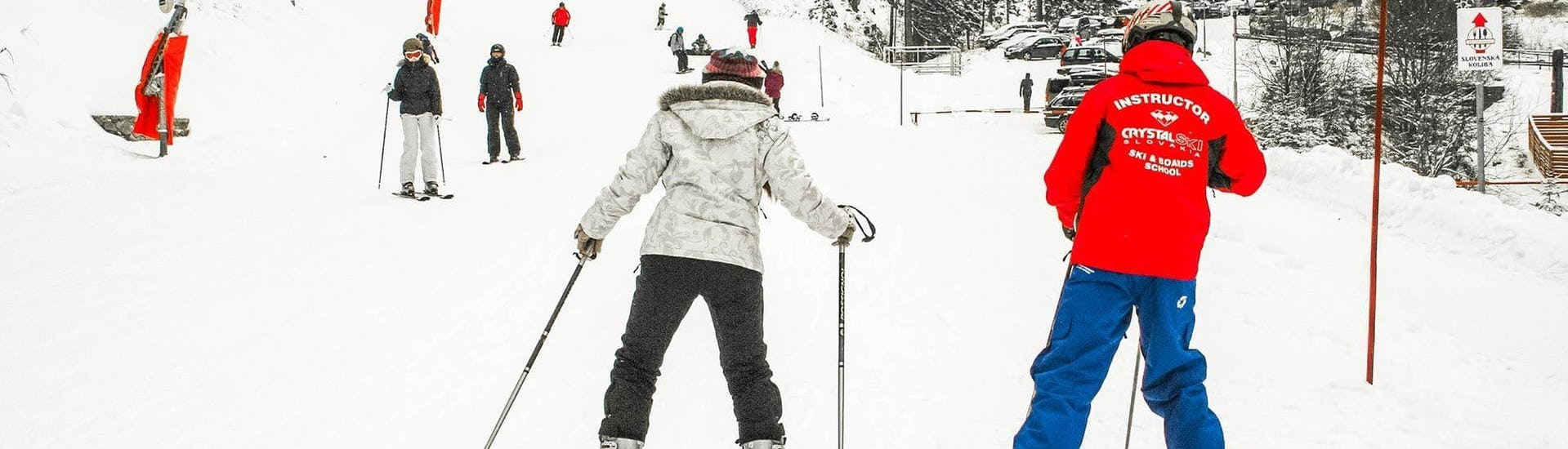 During the Private Ski Lessons for Adults - All Levels, an adult skier is benefiting from the full attention of her ski instructor from the ski school Crystal Ski.