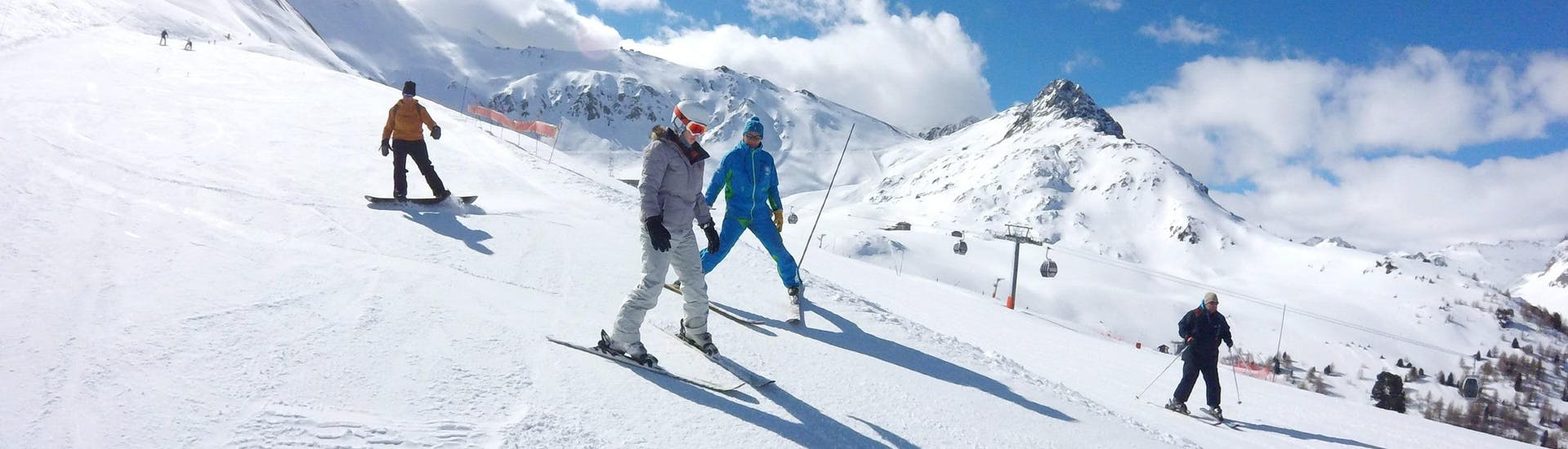 A skier is learning to ski thanks to the help of her ski instructor from the ski school ESI Valfréjus during her Private Ski Lessons for Adults - All Levels.