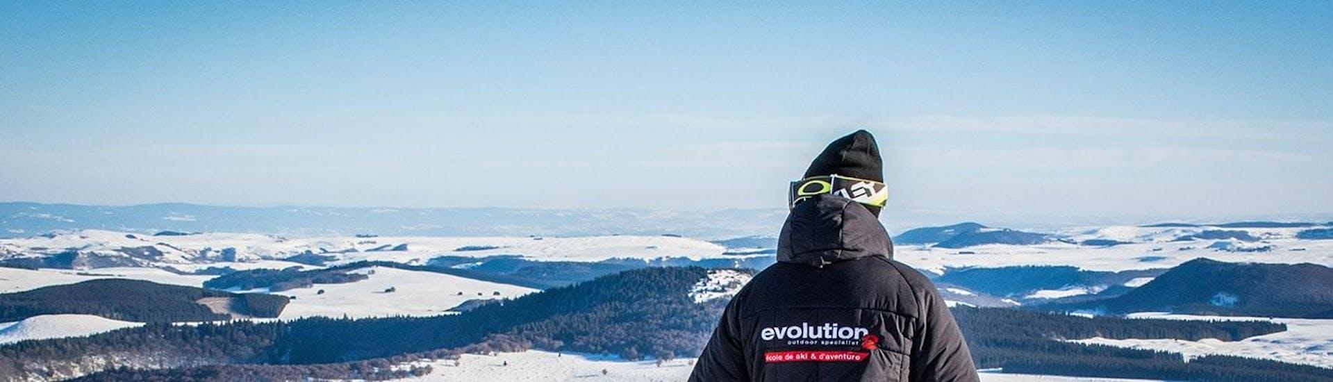Un skieur contemple le paysage enneigé à ses pieds pendant son Cours particulier de ski pour Enfants - Tous âges avec l'école de ski Evolution 2 Super Besse.