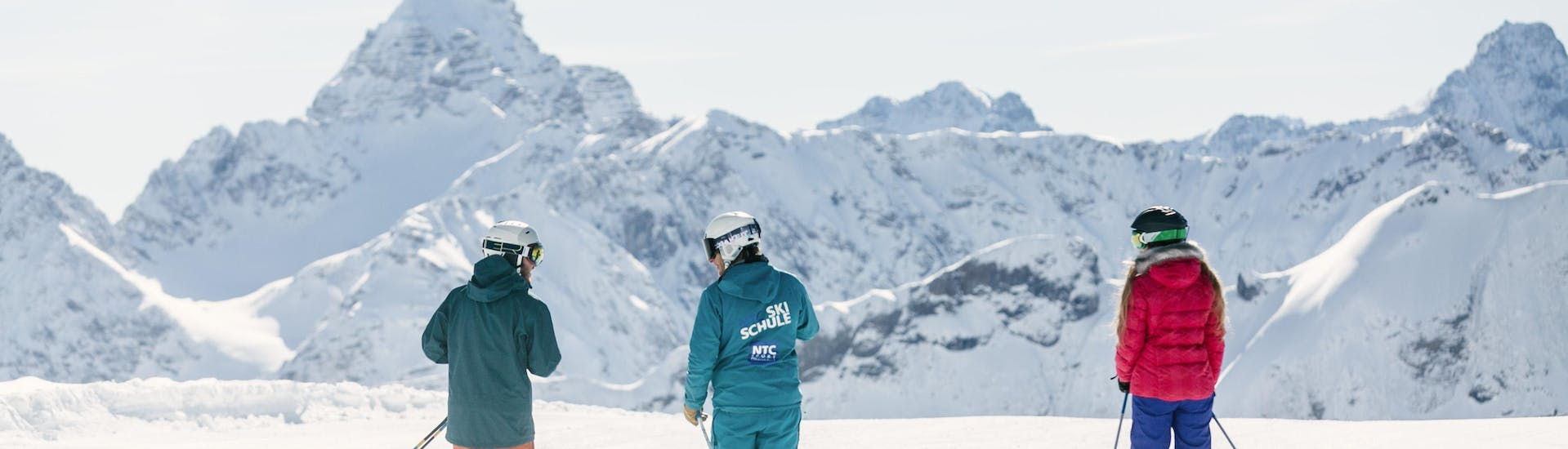 Two adults are learning how to ski for the first time during the Private Ski Lessons for Adults - All Levels with support from the ski instructor from the ski school NTC Skischule Oberstdorf.
