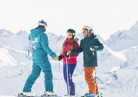 Two adults are enjoying the tailored-made Private Ski Lessons for Adults - All Levels under the guidance of an instructor from the ski school NTC Skischule Oberstdorf.