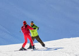 A ski instructor is helping a man to make the first descents, private ski lessons for adults - all levels at the ski school Scuola di Sci Abetone allow him to be accompanied individually.