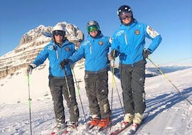 Some private instructors of the Private Ski Lessons for Adults - All Levels organized by the ski school Scuola di Sci Pinzolo in the Val Rendena ski resort are smiling at the camera on a sunny slope.