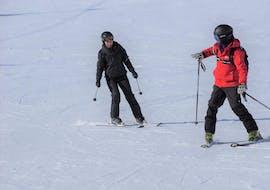 Ein Skilehrer der Ski- und Snowboardschule Vacancia bringt einem Teilnehmer der Aktivität Privater Skikurs für Erwachsene - Alle Levels das Skifahren bei.