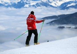 Un moniteur de ski de l'École Suisse de Ski Crosets-Champoussin se tient au sommet d'une montagne pendant un Cours particulier de ski pour Adultes - Tous niveaux.