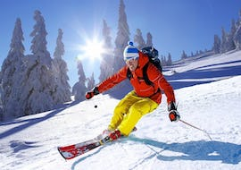 A skier is skiing down a snowy slope during hisPrivate Ski Lessons for Adults - All Levels with the ski school Snocool in Tignes.