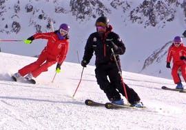 A ski instructor from the Escuela Ski Cerler teaches a student how to ski down the piste with the correct technique during the Private Ski Lessons for Adults for all Levels.