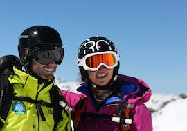 A skier and her instructor from the ski school Prosneige Méribel are smiling to the camera in front of a snowy landscape during theirPrivate Ski Lessons for Adults - High Season.
