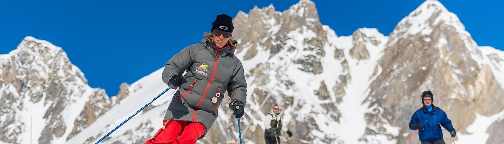 Des skieurs suivent leur moniteur de ski de l'école de ski Evolution 2 Tignes le long d'une pente enneigée pendant leur Cours particulier de ski Adultes - Vacances - Après-midi.