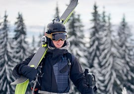 A skier is carrying his ski equipment to his Private Ski Lessons for Adults - Holidays with the ski school Moonshot La Bresse.