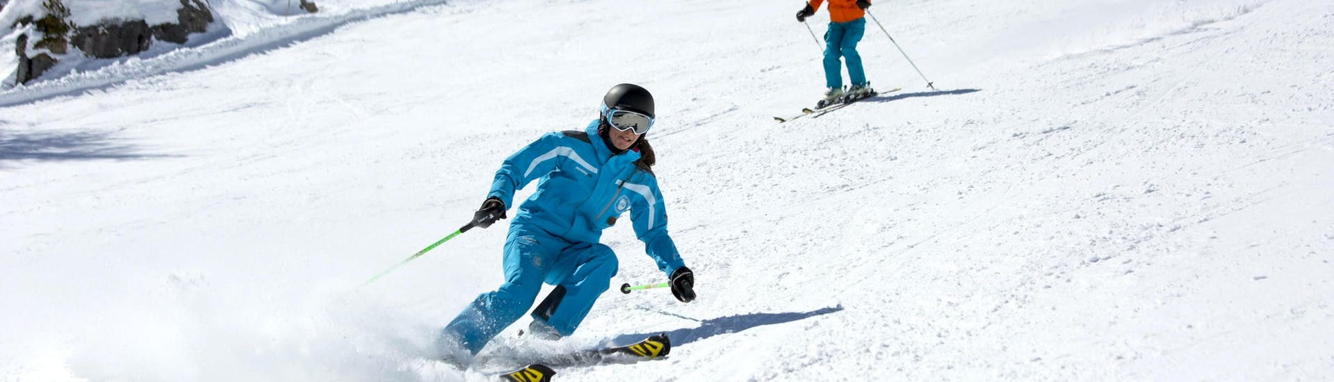 A skier is skiing down a snowy slope behind their ski instructor from the ski school ESI Font Romeu during their Private Ski Lessons for Adults - Low Season - All Levels.