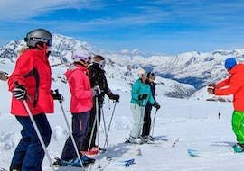 A group of adults is listening to their ski instructor from the ski school Evolution 2 Val d'Isère before the start of the Private Ski Lessons for Adults - Low Season - All Levels.