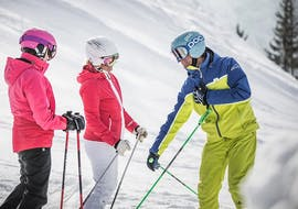 During the private ski lessons for adults in the SalzburgerLand region, the ski instructor from deinskicoach.at explains the right skiing technique to two women.