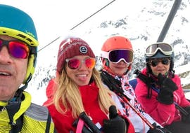 Skiers are sitting in a chairlift to reach the slopes they are going to ski down during their Private Ski Lessons for Adults of All Levels with the ski school ESF Aussois.