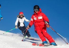 A skier is skiing down a slope behind their ski instructor from the ski school ESF La Foux d'Allos during their Private Ski Lessons for Adults of All Levels.