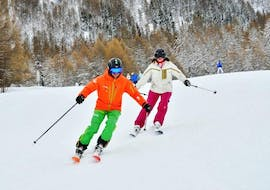 A skier is following her ski instructor from the ski school Evolution 2 La Plagne Montchavin - Les Coches on the slope during her Private Ski Lessons for Adults of All Levels.