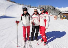 Three ski intructors of Hansis Skischule Steinach am Brenner are posing for a picture on the slopes of Bergeralm where they offer Private Ski Lessons for Adults of All Levels.