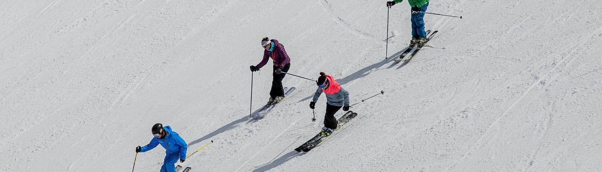 Three skieres are following their ski instructor from the ski school Ski Cool in skiing down a ski slope during one of their Private Ski Lessons for Adults - School Holiday - All Levels in the ski resort of Val Thorens.