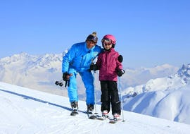 Un skieur et son moniteur de ski de l'école de ski ESI Valfréjus se tiennent devant un paysage de montagnes enneigées pendant leur Cours particulier de ski pour Enfants - Tous âges.