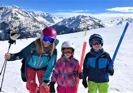 Zwei Teilnehmer des Angebots Privater Kinder Skikurs - Alle Altersgruppen der Ski- und Snowboardschule SNOWLINES Sölden lächeln gemeinsam mit ihrem Skilehrer in die Kamera.