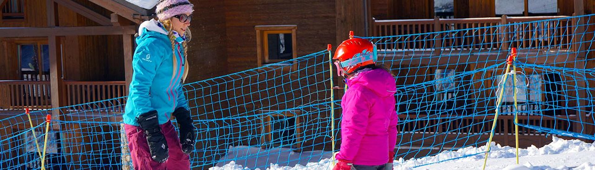 A child takes the first steps on skis during the Private Ski Lessons for Kids - All Ages and is guided by an experienced instructor from the ski school Snocool.