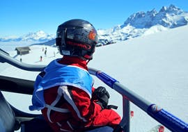 A young child is sitting in a chairlift on his way to his Private Ski Lessons for Kids - All Ages with the Swiss Ski School Les Crosets-Champoussin.