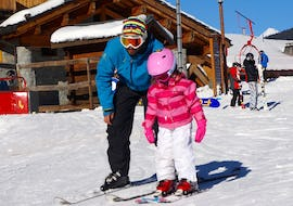 A young skier is learning how to ski with the support of her ski instructor from the ski school Snocool in Tignes during her Private Ski Lessons for Kids - All Ages.