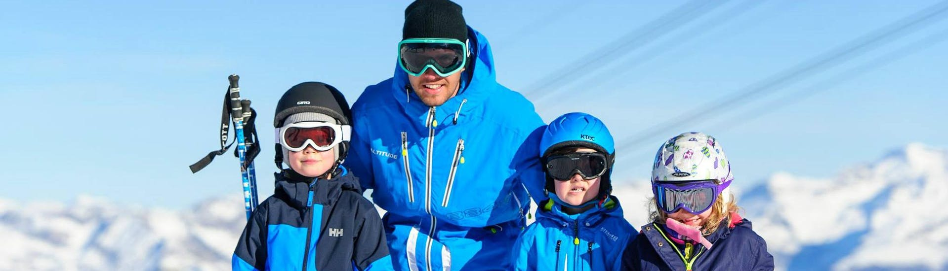 A ski instructor of Altitude Ski School Zermatt is posing for a photo with his students during the Private Ski Lessons for Kids - All Levels.