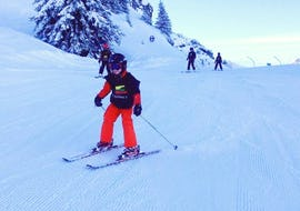 A kid is skiing down a snowy slope on their Private Ski Lessons for Kids - All Levels with the ski school Evolution 2 Morzine.