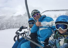 Two children with their ski instructor from the ESI Easy2Ride Morzine ski school smile at the camera as they take the lifts to join theirPrivate Ski Lessons for Kids - All Levels - Low Season.