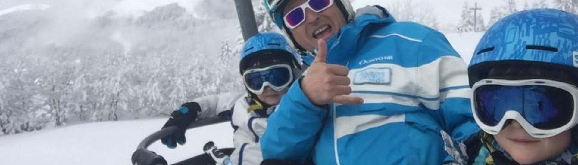 Deux enfants avec leur moniteur de ski de l'école de ski ESI Easy2Ride Morzine sourient à l'appareil photo tandis qu'ils empruntent les remontées mécaniques pour rejoindre leur Cours particulier de ski pour Enfants - Basse saison.