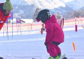 Ein kleiner Skifahrer macht unter der Aufsicht eines erfahrenen Skilehrers der Skischule Neue Skischule Oberstdorf im Rahmen des Angebots Privater Kinder Skikurs - Alle Levels seine ersten Schritte auf Skiern.