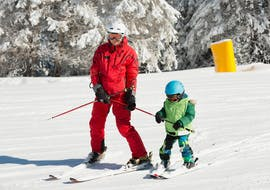 A ski instructor is helping a child to make the first descents, the private ski lessons for kids - all levels at the ski school Scuola di Sci Abetone allow the child to be followed individually.