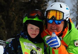 Private Ski Lessons for Kids - All Levels of the Folgarida Aevolution Ski School are just finished, teacher and child smile at the camera.