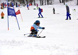 A young skier is trying to master a slope in the Via Lattea ski resort in Sestriere during the Private Ski Lessons for Kids - All Levels organized by the ski school Scuola di Sci Olimpionica.