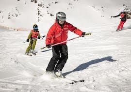 Ein Skilehrer der Ski- und Snowboardschule Vacancia zeigt einem Kind während der Aktivität Privater Kinder Skikurs - Alle Levels die richtige Skitechnik.
