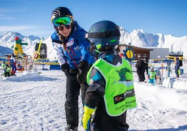 A ski instructor holds a child in her hand during some Private Ski Lessons for Kids - All Levels of the ski school Skischule Ischgl Schneesport Akademie.