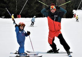 During the Private Ski Lessons for Kids - All Levels, a small kid is learning how to ski under the supervision of an experienced ski instructor from the ski school SnowMonkey in Špindlerův Mlýn.