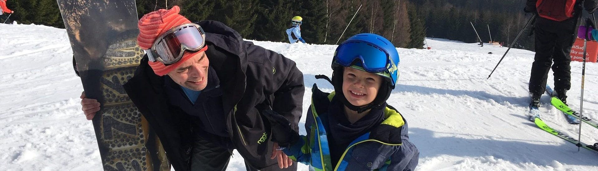 A small boy is enjoying the Private Ski Lessons for Kids - All Levels with his ski instructor from the ski school SnowMonkey.