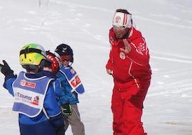 Trois enfants suivent leur moniteur de ski de l'école de ski suisse La Tzoumaz pendant leur Cours particulier de ski Enfants (dès 2 ans) - Tous niveaux.