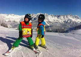 Two children stand happily on the piste and are happy about their learning progress during their Private Ski Lessons for Kids (from 3 y.) of All Levels from Skischule Ingrid Salvenmoser.