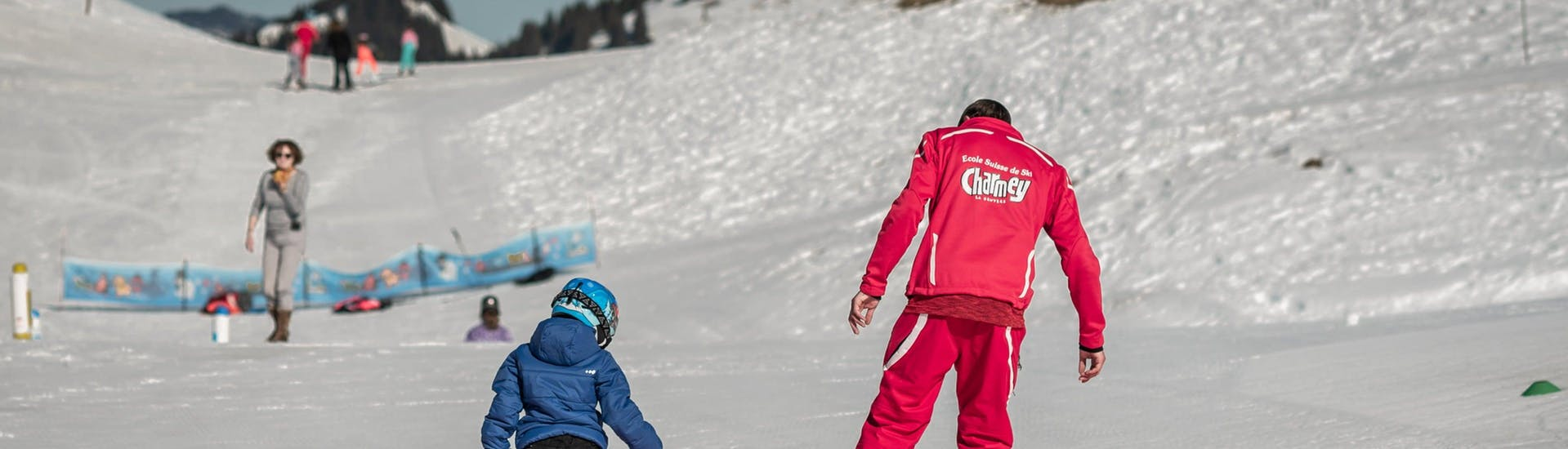 A kid is learning the basics of skiing with their ski instructor from the swiss ski school Charmey during their Private Ski Lessons for Kids (from 3 years) - All Levels.