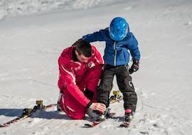 Un moniteur de ski de l'école de ski suisse Charmey aide un enfant à ajuster ses chaussures de ski pendant son Cours particulier de ski Enfants (dès 3 ans) - Tous niveaux.